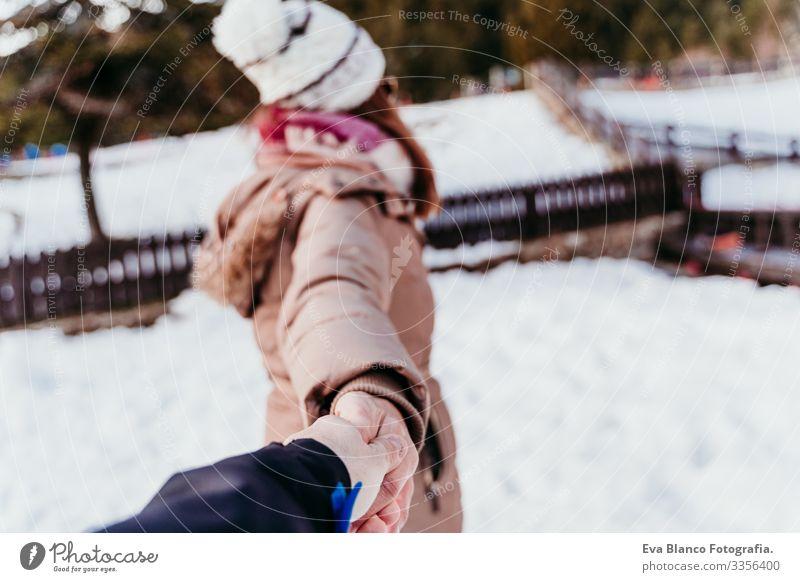 Folgen Sie mir. Frau und Mann halten sich an den Händen. pov. Wintersaison am Berg. Konzept der Liebe Hand mir folgen Schnee Freund Freundin Halt Valentinstag