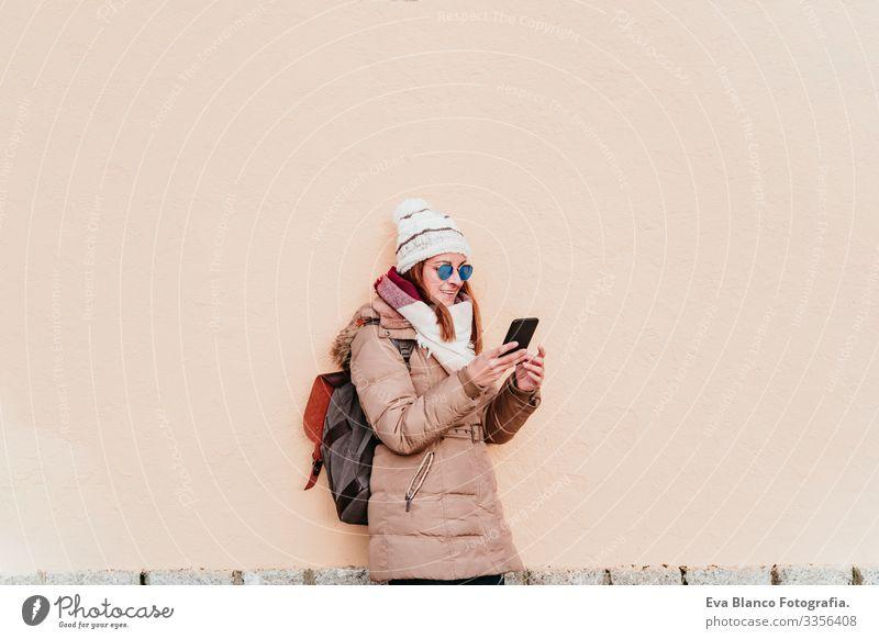 Frau, die ein Mobiltelefon über einem gelben Mauerhintergrund benutzt. Technik und Winterkonzept Außenaufnahme Großstadt Wand Handy Technik & Technologie