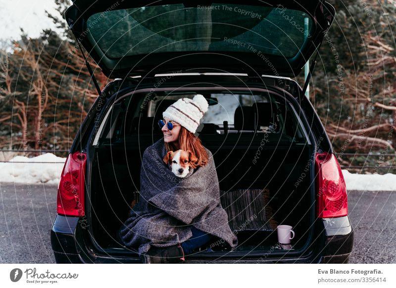 Frau und süßer Jack Russell Hund genießen draußen am Berg in das Auto. Reisekonzept. Wintersaison PKW Schnee Berge u. Gebirge Außenaufnahme