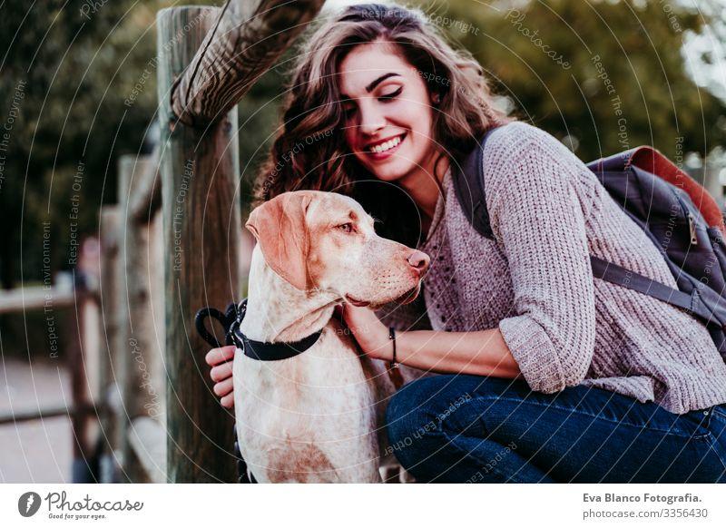 junge Frau und ihr Hund im Freien in einem Park mit einem See. sonniger Tag, Herbstsaison Porträt Jugendliche Außenaufnahme Liebe Haustier Besitzer