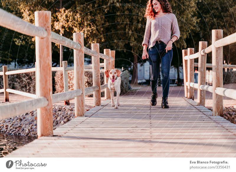 junge Frau und ihr Hund im Freien beim Spaziergang an einer Holzbrücke in einem Park mit See. sonniger Tag, Herbstzeit Porträt Jugendliche Außenaufnahme Liebe