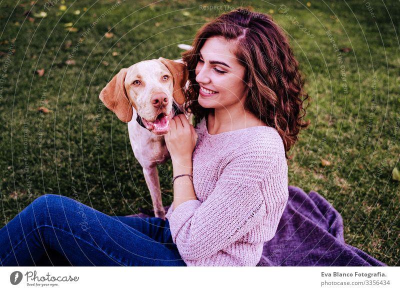 junge frau mit ihrem hund im park. sie umarmt den hund. herbstzeit Porträt Frau Hund Park Jugendliche Außenaufnahme Liebe Haustier Besitzer Sonnenstrahlen schön