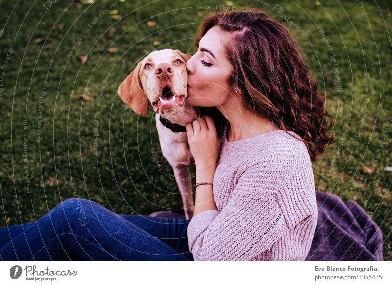 junge frau mit ihrem hund im park. sie küsst den hund. herbstzeit Porträt Frau Hund Park Jugendliche Außenaufnahme Liebe Haustier Besitzer Sonnenstrahlen schön