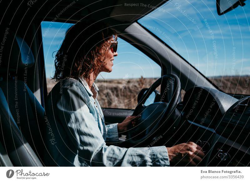 junge, schöne Frau am Steuer eines Autos. Reisekonzept Jugendliche fahren PKW Sonnenstrahlen Sonnenbrille Ferien & Urlaub & Reisen reisend Rad Laufwerk mieten