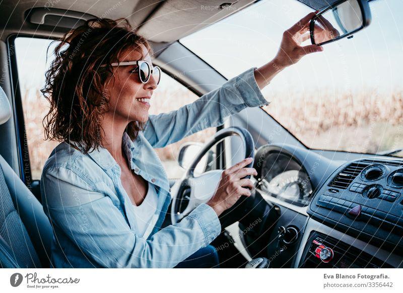 junge schöne Frau, die ein Auto fährt und den Rückspiegel verstellt. reisekonzept Jugendliche fahren PKW Sonnenstrahlen Sonnenbrille Ferien & Urlaub & Reisen