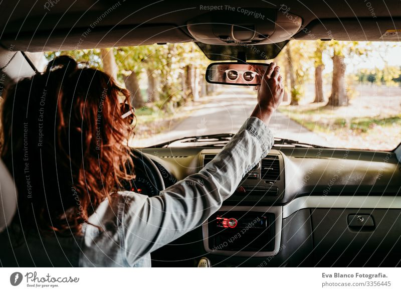 junge schöne frau beim autofahren. reisekonzept. ansicht von innen. weg der bäume straße Frau Jugendliche PKW Sonnenstrahlen Sonnenbrille