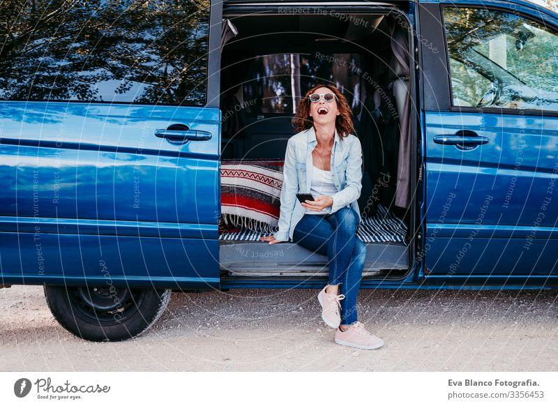 glückliche Frau, die in einem blauen Van sitzt und Spaß hat. reisekonzept Glück lachen Kleintransporter PKW Ferien & Urlaub & Reisen Handy genießend Freude