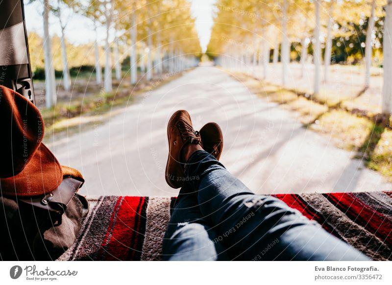 süßer jack russell hunde- und frauenbeine entspannen im van. reisekonzept. selektive fokussierung auf bäume Frau aussruhen Kleintransporter Beine unkenntlich