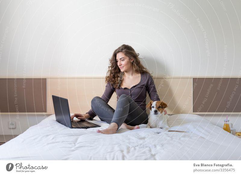 eine schöne junge Frau, die mit ihrem süßen kleinen Hund neben ihr auf dem Bett sitzt. Sie arbeitet am Laptop und lächelt. Haus, Wohnung und Lebensstil