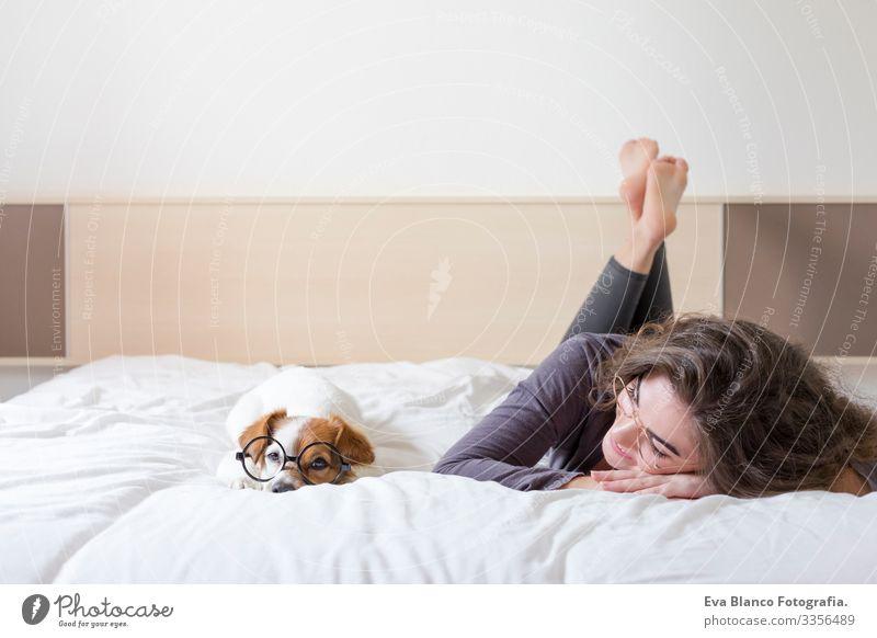 eine schöne junge Frau, die mit ihrem süßen kleinen Hund auf dem Bett liegt. Haus, Wohnung und Lebensstil gemütlich Müdigkeit träumen Stimmung kuscheln