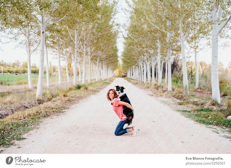 eine junge Frau, die mit ihrem süßen Border-Collie-Hund auf einem Baumpfad im Freien trainiert. Border Collie Kleintransporter Ferien & Urlaub & Reisen reisend