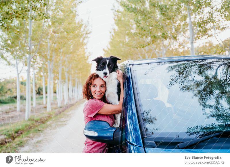 Frau, die ihren Border-Collie-Hund in einem Lieferwagen umarmt. Reisekonzept Border Collie Kleintransporter Van Leben Ferien & Urlaub & Reisen reisend Besitzer