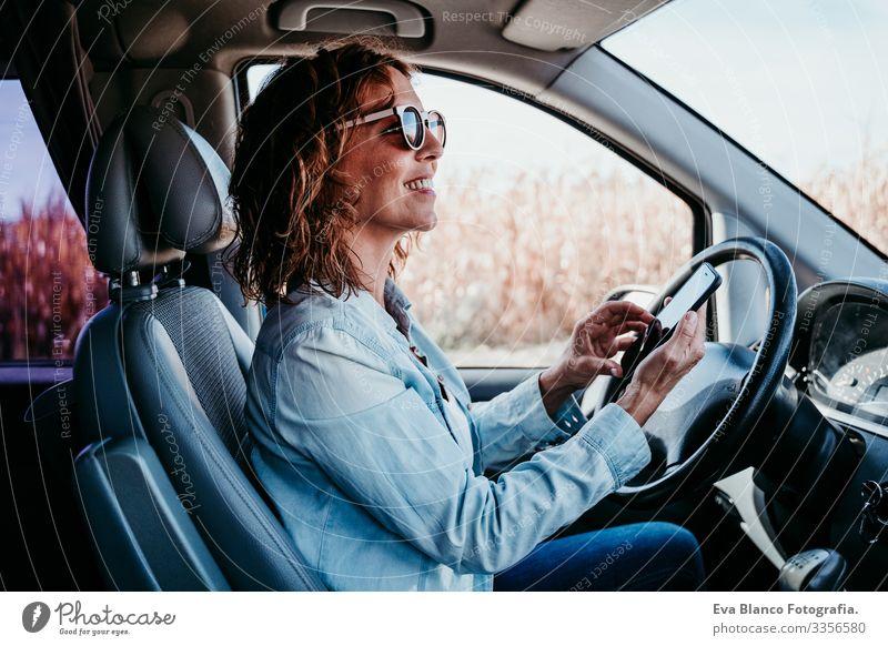 junge, schöne Frau, die im Auto mobil telefoniert. reisekonzept Handy Technik & Technologie benutzend Jugendliche fahren PKW Sonnenstrahlen Sonnenbrille