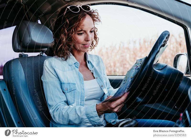junge schöne frau, die im auto eine karte liest. reisekonzept Landkarte lesen Frau Jugendliche fahren PKW Sonnenstrahlen Sonnenbrille Ferien & Urlaub & Reisen