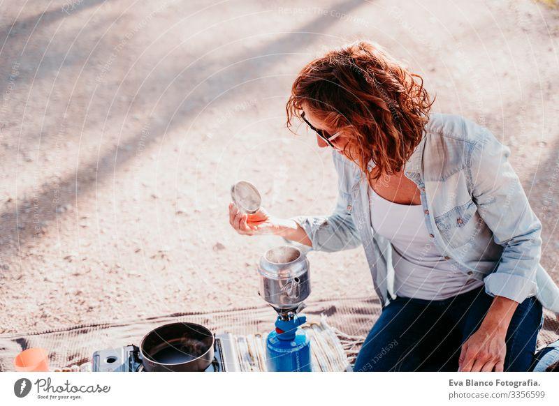 junge Frau, die im Freien mit Kanne und Herd Tee zubereitet. Camping-Konzept Jugendliche Topf Herd & Backofen Sonnenuntergang vorbereitend heiß Teekanne Kaffee