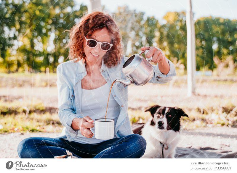 junge Frau, die im Freien Tee mit Kanne einschenkt. Benutzung des Kochers. Camping-Konzept Gießen Jugendliche te Topf Herd & Backofen Sonnenuntergang