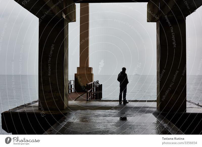 Der Mensch steht bei schlechtem Wetter allein auf einer Seebrücke. Freiheit Mann Erwachsene Nebel Denken Traurigkeit Einsamkeit Fürsorge Anlegestelle dramatisch