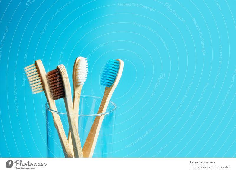 Zahnbürsten aus Holz mit einem Glasbecher auf blauem Hintergrund. Lifestyle Behandlung Wellness Leben Bad Umwelt Natur Verpackung Kunststoff frei frisch modern