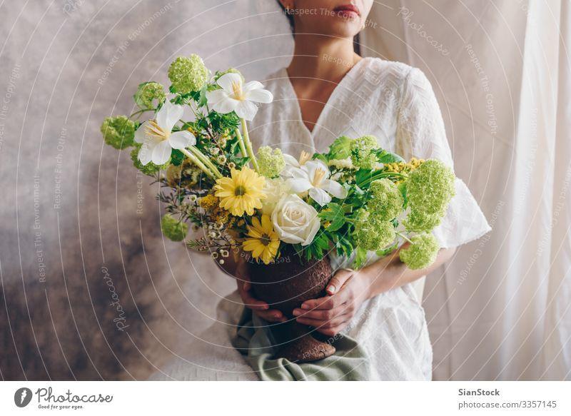 Junge Frau in einem weißen Kleid, die eine Vase mit Blumen hält. Lifestyle elegant Stil Glück schön Stuhl Hochzeit Erwachsene Lippen Hand brünett Blumenstrauß