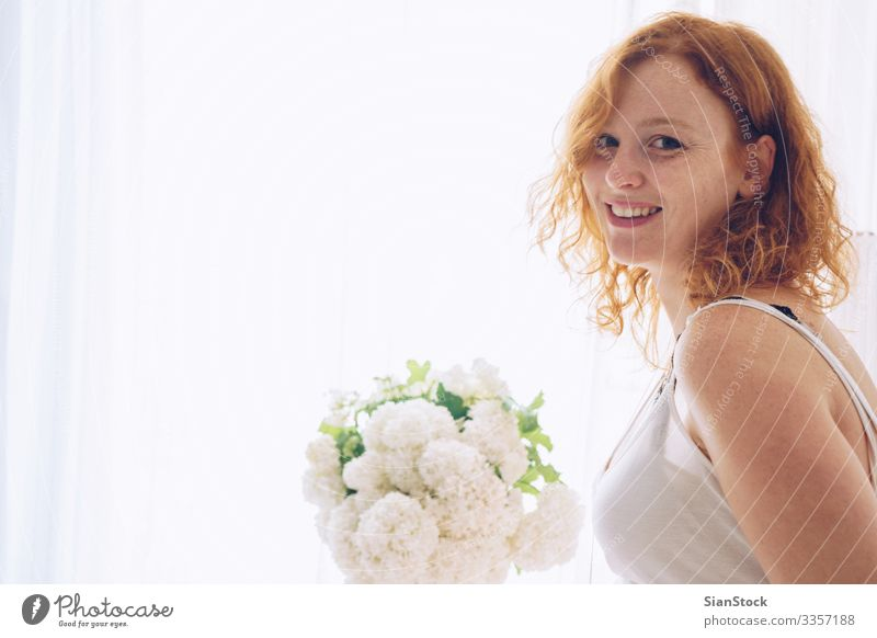 Porträt einer rothaarigen schönen Frau, die zu Hause am Fenster sitzt Haut Gesicht Schminke Mensch Erwachsene Blume Mode Lächeln Erotik natürlich niedlich weiß