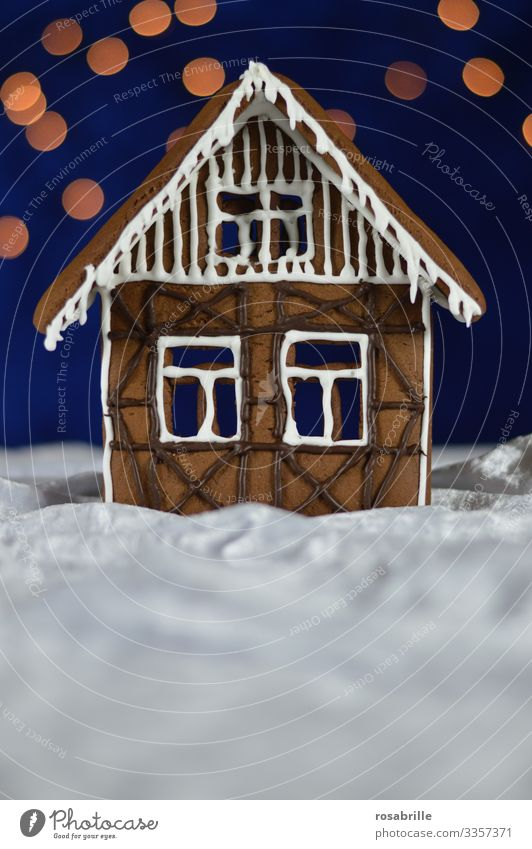 Lebkuchenhaus Fassade mit Zuckerguß und Schokoladenverzierung als Fachwerk auf weissem Samt, der wie Schnee aussieht, vor dunkelblauem Hintergrund mit Bokeh-Punkten als Sterne