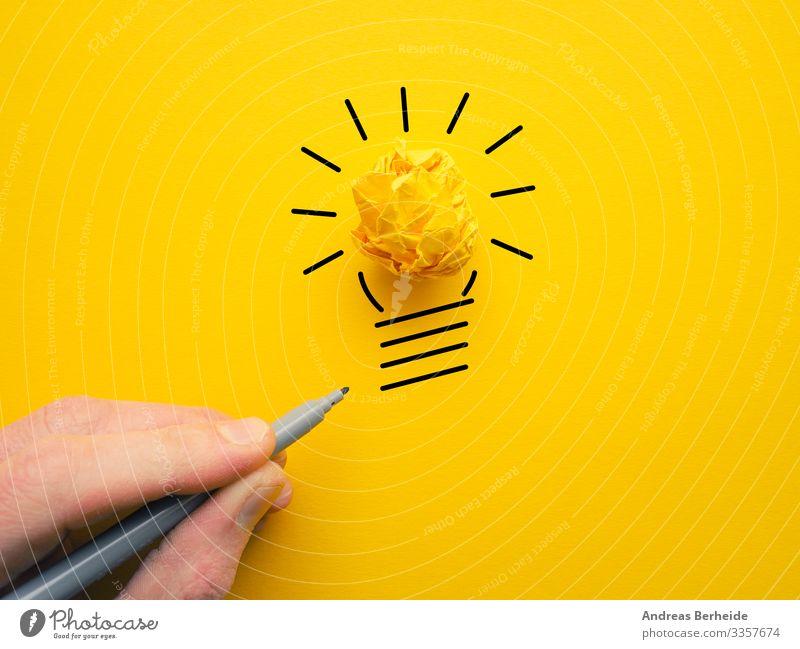 Gelbe zerknitterte Papierkugel als Glühbirne Knolle Hand Licht Idee Lampe Energie Konzept Zeichnung Geschäftsmann Kraft Elektrizität Business hell elektrisch