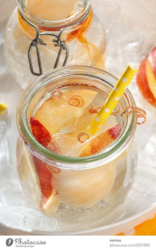 Kühles Erfrischungsgetränk mit Nektarine in Glas und gelbem Trinkhalm auf weißem Tablett voller Eiswürfel Frucht Getränk Vitamin Pfirsich Picknick Honigmelone