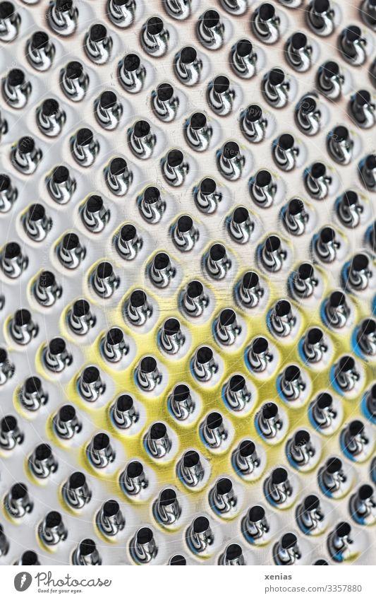 Makroaufnahme einer Küchenreibe mit gelben Fleck aus Edelmetall Reibe Essen zubereiten Metall glänzend rund Sauberkeit schwarz silber Futurismus Loch Reihe