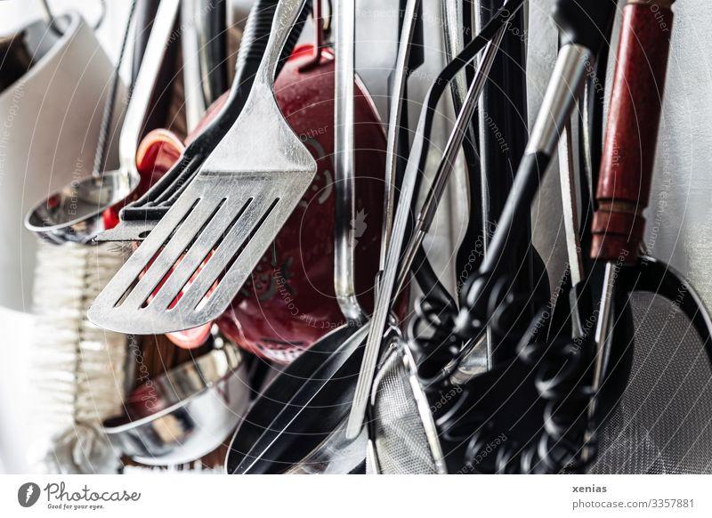 viele ungeordnete Küchengeräte hängen vor weißer Wand Pfannenheber Schöpflöffel Sieb Rührbesen Küchensieb Bürste Manuelles Küchengerät Metall Kunststoff