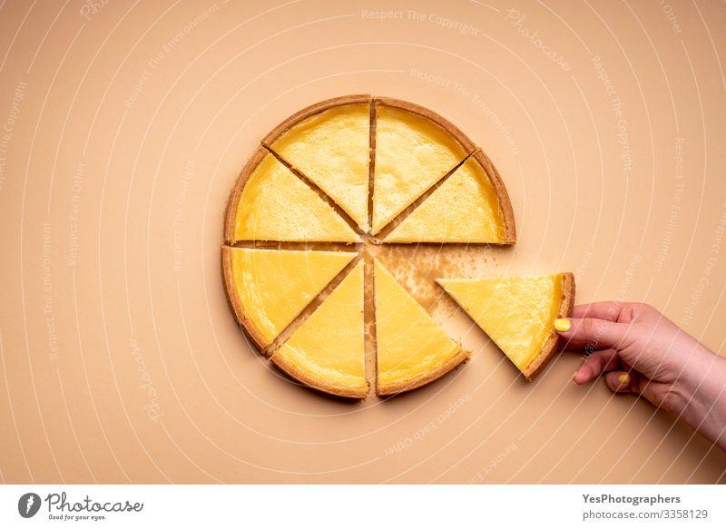 Käsekuchen auf einem cremefarbenen Hintergrund. Hand der Frau Lebensmittel Milcherzeugnisse Kuchen Dessert Süßwaren Essen frisch lecker Tradition obere Ansicht