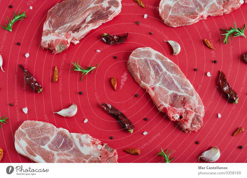 Rohe Fleischsteaks mit Gewürzen auf rotem Grund. Flacher Schlag. Kräuter & Gewürze Ernährung Essen Abendessen Diät füttern frisch saftig grün Werbung