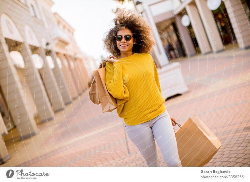 Junge schwarze Frau mit lockigem Haar beim Einkaufen Lifestyle Stil Glück schön Haare & Frisuren Mensch Junge Frau Jugendliche Erwachsene 1 18-30 Jahre Straße