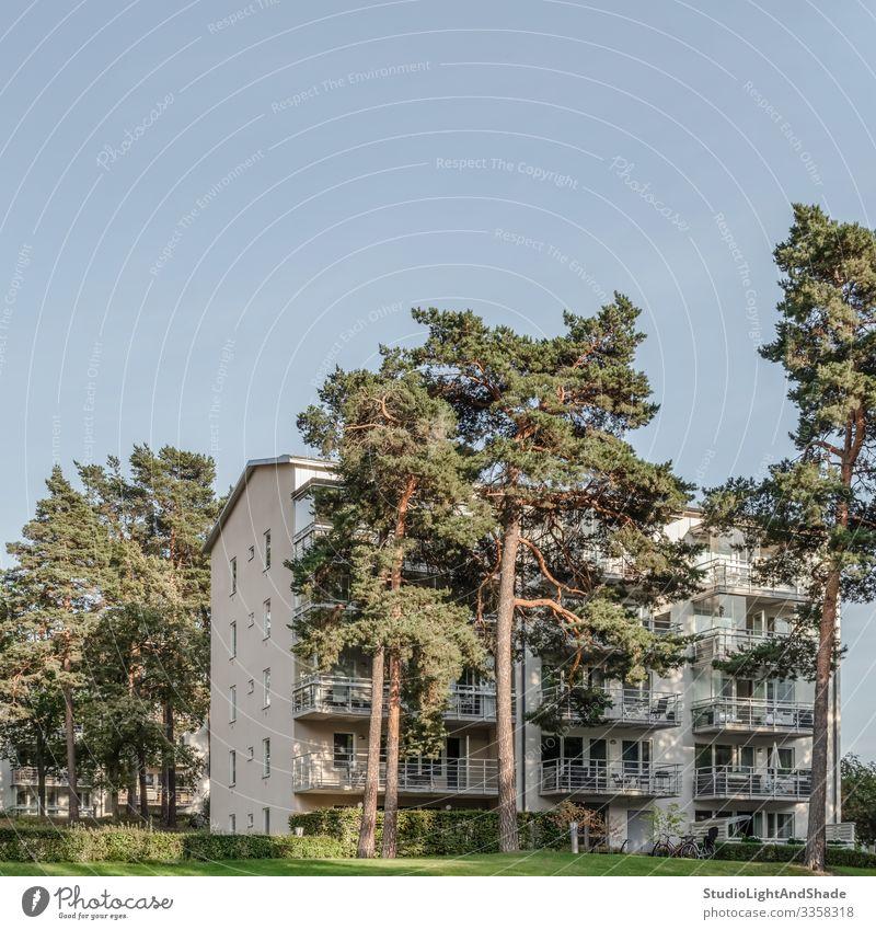 Kiefern und Wohngebäude Lifestyle Haus Umwelt Pflanze Himmel Baum Stadt Gebäude Architektur Fassade Balkon modern Sauberkeit blau grün nadelhaltig Europa