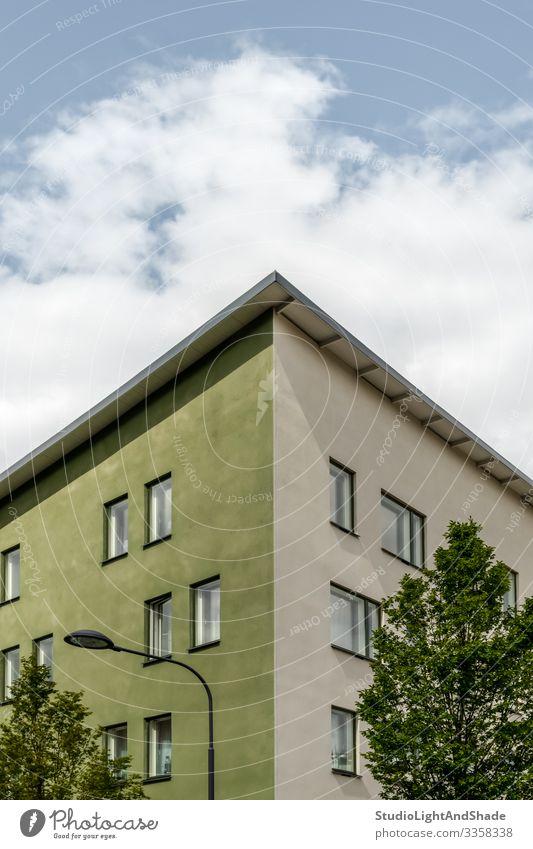 Ecke eines grünen Gebäudes und Bäume Lifestyle Haus Lampe Umwelt Pflanze Himmel Wolken Baum Stadt Architektur Fassade Straße einfach modern neu Sauberkeit blau