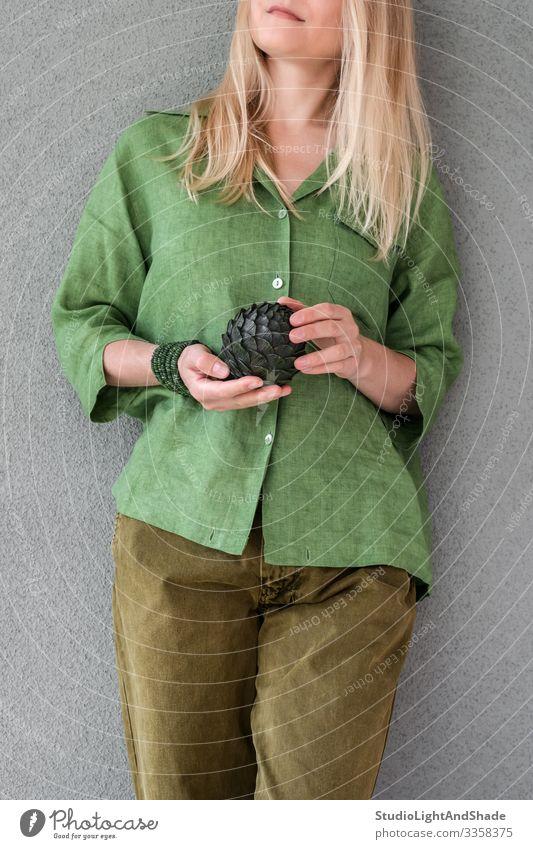 Frau in grüner Kleidung mit Artischocke schön Sommer Mensch Junge Frau Jugendliche Erwachsene Kunst Mode Bekleidung Hemd Hose Jeanshose blond langhaarig Metall