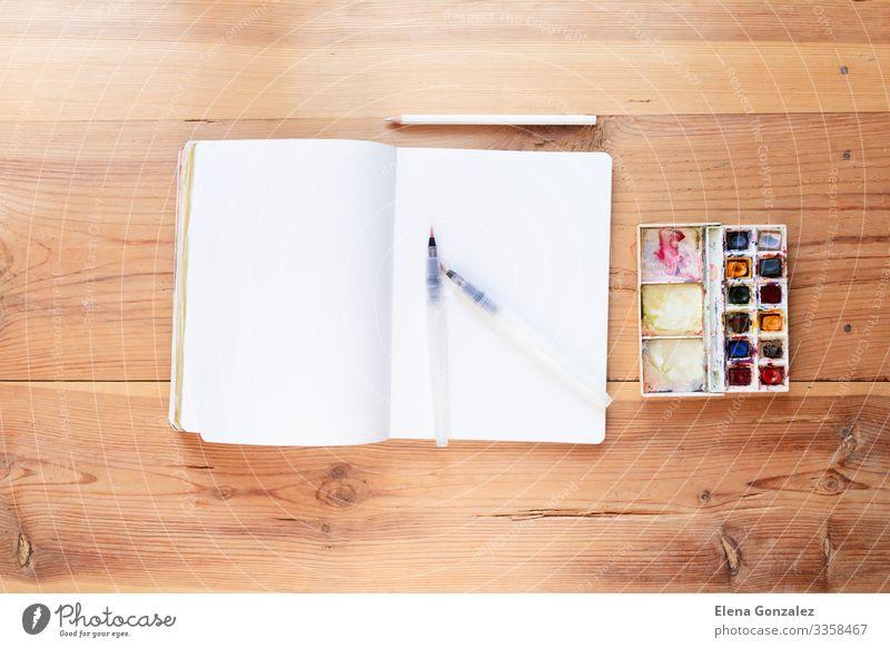 Aquarellfarben und Pinsel, mit denen neue Gemälde entstehen. Schule lernen Arbeit & Erwerbstätigkeit Arbeitsplatz Papier zeichnen Begeisterung Farbe Inspiration