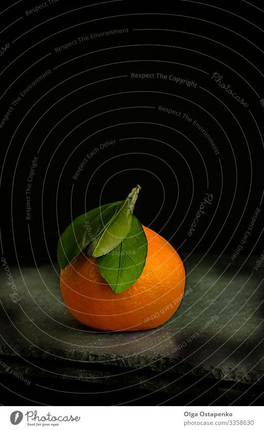 reife, saftige Mandarine mit grünem Blatt auf schwarzem Grund Clementine Vegetarische Ernährung süß organisch Gesunde Ernährung Frucht tropisch frisch Zirkus