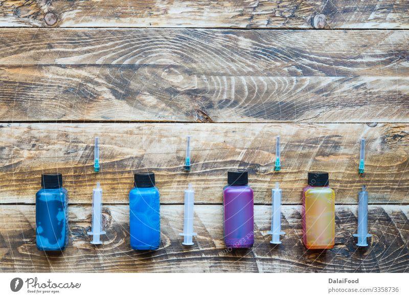 Tinte für Druckerspritzen mit Holzuntergrund Büro Container Accessoire Kunststoff Tropfen blau gelb rot schwarz weiß Farbe Hintergrund Patrone