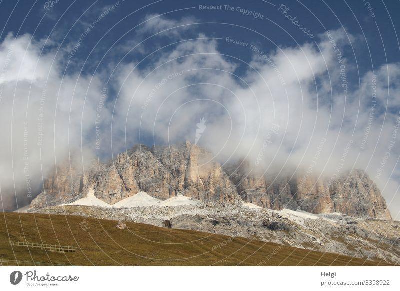Berge der Alpen hüllen sich in dicke Wolken vor blauem Himmel Berge u. Gebirge Dolomiten Sellajoch Herbst Wiese wandern Bergsteigen Umwelt Natur Landschaft