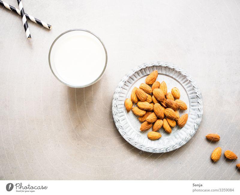 Ein Glas Mandelmilch und ein Teller mit Mandeln Lebensmittel Milcherzeugnisse Ernährung Frühstück Bioprodukte Vegetarische Ernährung Diät Getränk Trinkhalm