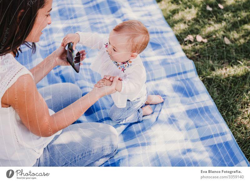 junge Mutter und glückliches Baby, das im Freien mit dem Handy telefoniert. technologiekonzept Technik & Technologie Zusammensein Kind Kindererziehung Mädchen
