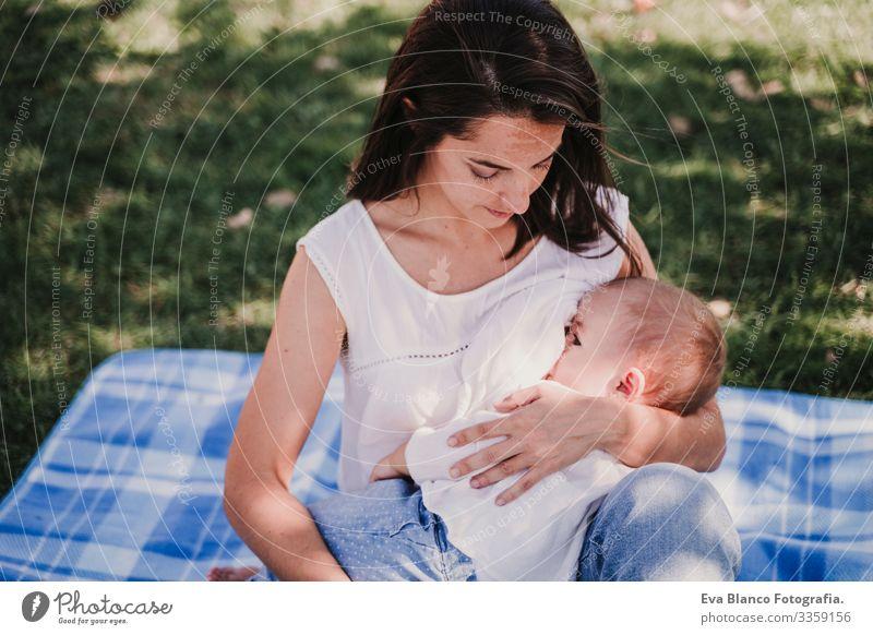 junge Mutter, die im Park im Freien ihr Baby stillt, glückliches Familienkonzept. liebe Mutter-Tochter stillen Milch Essen Kind Kindererziehung Mädchen