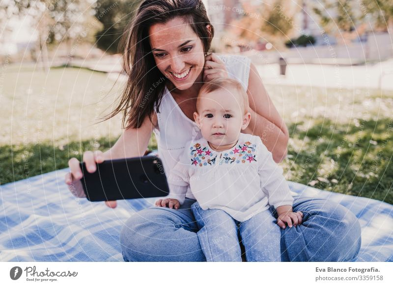 junge Mutter und glückliches Baby, das im Freien mit dem Handy telefoniert. technologiekonzept Kind Kindererziehung Mädchen Freude Sonnenstrahlen Eltern