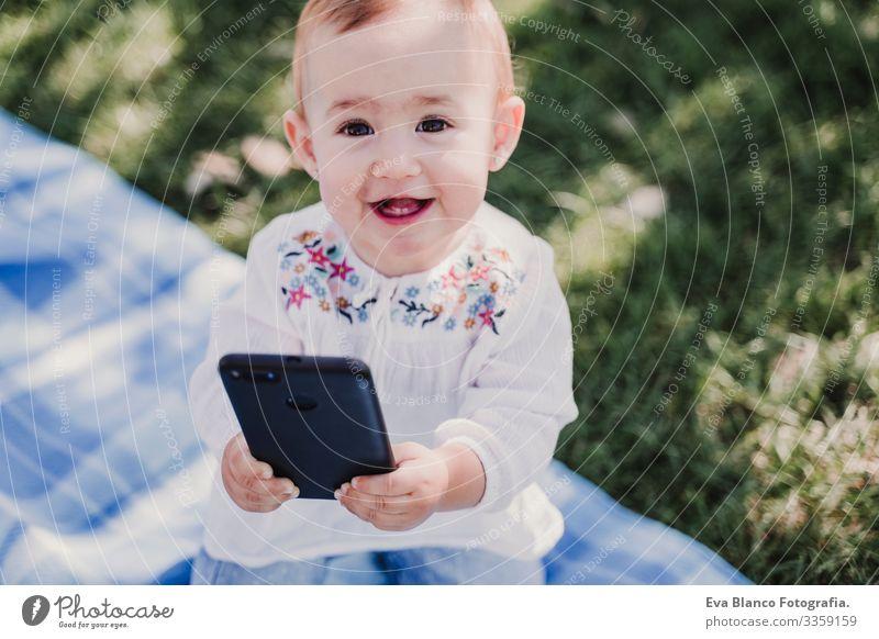 glückliches Baby, das sein Handy im Freien benutzt. technologiekonzept Mutter Technik & Technologie Zusammensein Kind Kindererziehung Mädchen Freude
