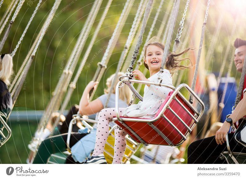 Kleines Mädchen mit Spaß auf dem Kettenkarussell. Glückliche Sommer-Erinnerungen. Unbeschwerte Kindheit und Glück Aktion Aktivität Abenteuer Vergnügen schön