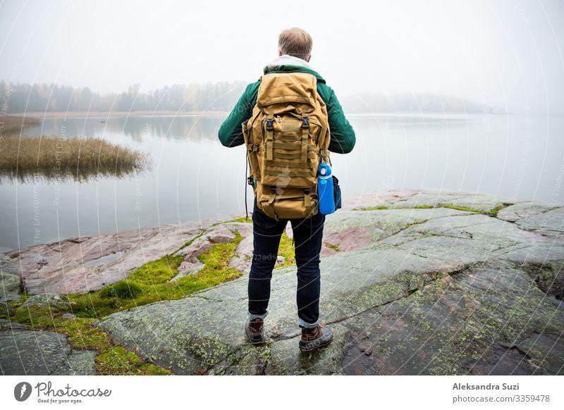 Ein reifer Mann erkundet Finnland im Herbst und schaut in den Nebel. Wanderer mit großem Rucksack auf moosigem Fels stehend. Skandinavische Landschaft mit nebligem Meer und Herbstwald. Rückenansicht