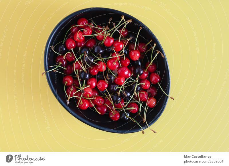 Schwarze Keramikschale mit Wildkirschen auf gelbem Grund. Lebensmittel Frucht Dessert Ernährung Vegetarische Ernährung Diät Schalen & Schüsseln