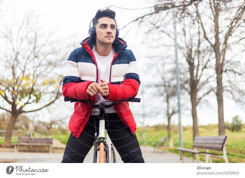 Hübscher, hipper junger Mann, der eine Fahrradtour genießt und ein Smartphone benutzt, während er über Kopfhörer Musik hört Straße Menschen männlich Person