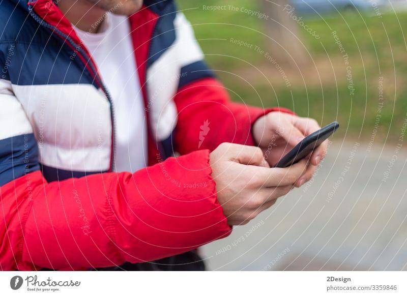 Junger Mann mit einem Smartphone in der Hand schreibt draußen auf der Straße SMS Mobile Beteiligung benutzend Telefon Technik & Technologie Handy Gerät