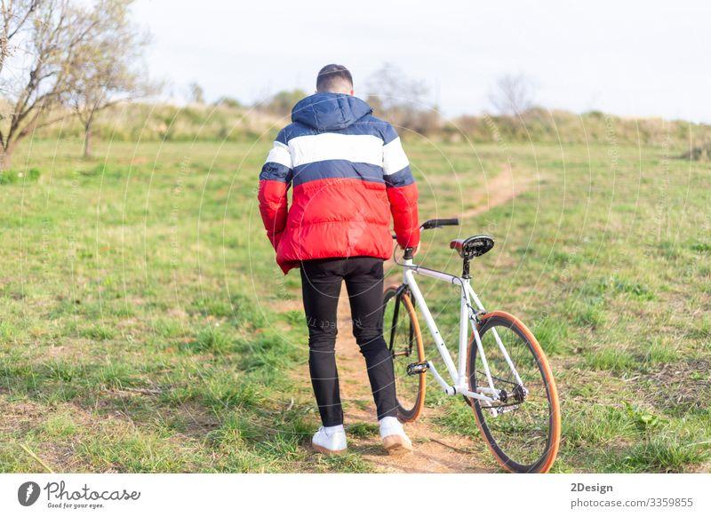 Rückansicht eines jungen Mannes, der mit einem feststehenden Fahrrad auf einem Park läuft Lifestyle Stil Glück Freizeit & Hobby Musik Telefon Handy PDA